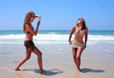Zwei reizvolle junge Frauen, die auf dem Strand auf Ferien oder Feiertag spielen Stockbild