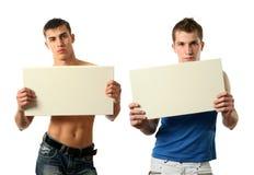 Zwei reizvolle Männer, die ein Exemplar zeigen, sperren unbelegte Anschlagtafel stockbild