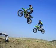 Zwei Rennläufer, die in einer Luft während motocros Wettbewerbs springen Stockbilder