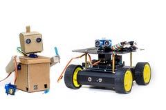 Zwei Roboter, die zusammen auf einem weißen Hintergrund stehen Stockfotografie