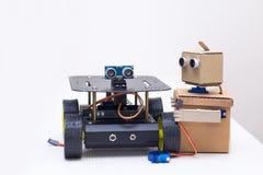 Zwei Roboter sind auf dem Tisch auf einem weißen Hintergrund Lizenzfreie Stockfotos