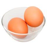 Zwei rohe Eier in der Glasschüssel Stockfotos