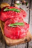 Zwei rohe Steaks mit Rosmarin, Knoblauch, Salz und Pfeffer lizenzfreie stockfotografie