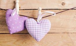 Zwei romantische purpurrote Herzen verdübelt auf einer Linie lizenzfreies stockbild
