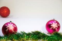 Zwei rosa festliche Bälle im Fokus mit einem roten Ball in der Ecke unscharf Lizenzfreies Stockfoto