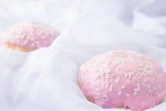Zwei rosa glasig-glänzende Schaumgummiringe mit besprüht Lizenzfreies Stockfoto