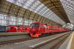 Zwei Rot Aeroexpress-Züge, die an einer Landungsplattform des Bahnhofs- und Shukhov-`s Stahl-undglasdachs Moskaus Kiyevskaya steh Lizenzfreies Stockbild