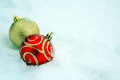 Zwei rot und Goldbunte Weihnachtsbälle im Schnee lizenzfreies stockfoto