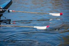 Zwei rot und weiße Ruder herausgehoben vom Wasser Lizenzfreie Stockfotos