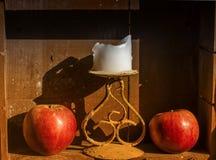 Zwei rote Äpfel und Kerze lizenzfreie stockfotos