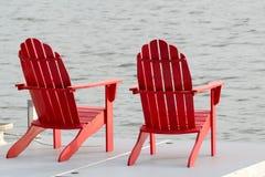 Zwei rote Adirondack Stühle Lizenzfreie Stockfotos