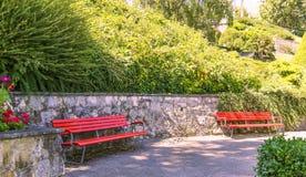 Zwei rote Bänke im schönen Park, Nyon Lizenzfreies Stockbild