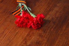 Zwei rote Blume Symbole des Sieges im Großen patriotischen Krieg auf hölzernem Stockfotografie