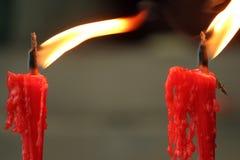 Zwei rote brennende Kerzen vor dem buddhistischen Tempel Stockfotografie
