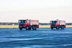 Zwei rote Flugfeldlöschfahrzeuge am Flughafen Lizenzfreie Stockfotografie