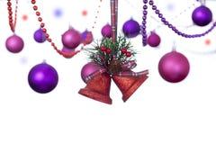 Zwei rote Funkelnglocken, die an einem Schottenstoffband mit Weihnachtsflitter hängen Lizenzfreie Stockbilder