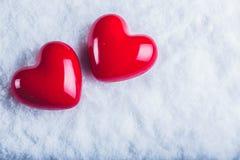 Zwei rote glatte Herzen auf einem eisigen weißen Schneehintergrund Liebe und St-Valentinsgrußkonzept Lizenzfreies Stockfoto