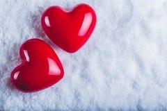Zwei rote glatte Herzen auf einem eisigen weißen Schneehintergrund Liebe und St-Valentinsgrußkonzept Stockfotografie