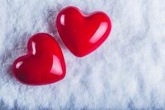 Zwei rote glatte Herzen auf einem eisigen weißen Schneehintergrund Liebe und St-Valentinsgrußkonzept Stockbild