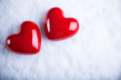 Zwei rote glatte Herzen auf einem eisigen weißen Schneehintergrund Liebe und St-Valentinsgrußkonzept Stockfotos