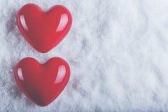 Zwei rote glatte Herzen auf einem eisigen weißen Schneehintergrund Liebe und St-Valentinsgrußkonzept Lizenzfreie Stockfotografie