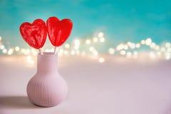 Zwei rote Herz-Form-Süßigkeits-Lutscher auf Stöcken in der Vasen-Nachahmung von Blumen Türkis-Hintergrund-Valentinsgruß Stockbild