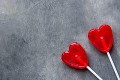 Zwei rote Herz-Form-Süßigkeits-Lutscher auf Stöcken auf dunklem Steinhintergrund Valentine Romantic Love Greeting Card Stockfotografie