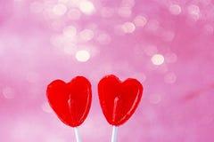 Zwei rote Herz-Form-Süßigkeits-Lutscher auf Stock-rosa pinkfarbenem Hintergrund mit funkelnden Bokeh-Lichtern Valentine Romantic  Stockbilder