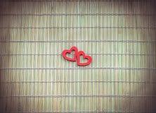 Zwei rote Herzen auf Bambusserviette Lizenzfreie Stockfotografie