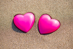 Zwei rote Herzen auf dem Strand, der Liebe symbolisiert Lizenzfreies Stockfoto