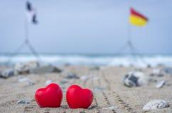 Zwei rote Herzen auf dem Strand mit Brandungsflaggen im Hintergrund Lizenzfreie Stockfotos