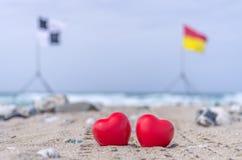 Zwei rote Herzen auf dem Strand mit Brandungsflaggen im Hintergrund Lizenzfreie Stockfotografie