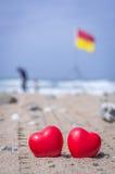 Zwei rote Herzen auf dem Strand mit Brandungsflaggen im Hintergrund Stockfoto