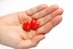 Zwei rote Herzen auf der Hand des Mannes auf weißem Hintergrund. Herzen auf der Palme Lizenzfreie Stockbilder