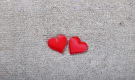 Zwei rote Herzen auf einem grauen Hintergrund Stockfotos