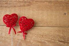 Zwei rote Herzen auf einem hölzernen Hintergrund getrennt auf weißem, selektivem Fokus stockbild