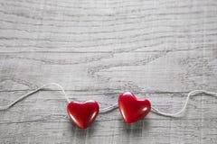 Zwei rote Herzen auf einem hölzernen schäbigen Hintergrund für Valentinsgruß. Stockfotografie
