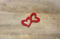 Zwei rote Herzen auf hölzernem Hintergrund Stockfotos