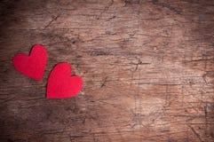 Zwei rote Herzen auf Holztisch Stockfotografie
