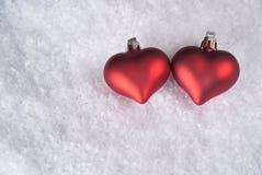 Zwei rote Herzen auf Schnee Stockbild