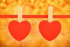 Zwei rote Herzen am Band über goldener Funkelnunschärfe Lizenzfreie Stockfotos