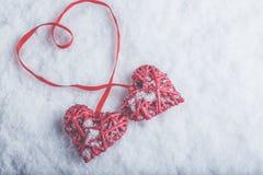 Zwei rote Herzen der schönen romantischen Weinlese gebunden zusammen mit Band auf weißem Schneehintergrund Liebe und St.-Valentin Stockfoto