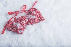 Zwei rote Herzen der schönen romantischen Weinlese gebunden zusammen mit Band auf weißem Schneehintergrund Liebe und St.-Valentin Lizenzfreie Stockbilder