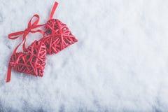 Zwei rote Herzen der schönen romantischen Weinlese gebunden zusammen mit Band auf weißem Schneehintergrund Liebe und St.-Valentin Stockfotos