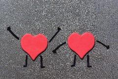 Zwei rote Herzen, die einem Mann mit den gemalten Händen und den Füßen auf einem grauen Hintergrund ähneln Valentinsgruß `s Tag L Lizenzfreie Stockbilder