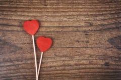 Zwei rote Herzen formen auf Stock über hölzernem Hintergrund Rote Rose und Inneres über Weiß Beschneidungspfad eingeschlossen Lizenzfreies Stockbild