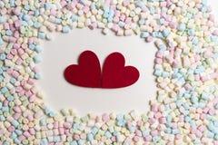 Zwei rote Herzen im Rahmen von bunten Minieibischen als Hintergrund Stockfotografie