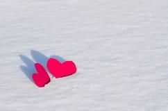 Zwei rote Herzen im Schnee Stockbild