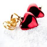 Zwei rote Herzen mit Goldbändern auf Schnee Stockbilder