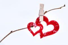Zwei rote Herzen mit Wäscheklammer und Schneeflocken auf einer Niederlassung als g Lizenzfreie Stockfotografie